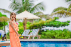 Cute little girl standing alone beside swimming pool Stock Photo