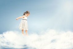 Cute little girl standing barefoot on clouds Stock Image