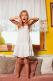 Cute little girl standing on the bed surprised Stock Images