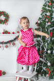 Cute little girl standing on a chair near  the Christmas tree Stock Images