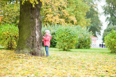 Cute little girl standing close to the tree Royalty Free Stock Image