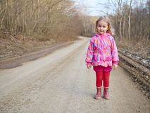 Cute little girl standing on a forest road Stock Photo