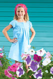 cute little girl standing in the garden surrounded by flowers. Stock Photos