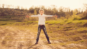 Cute little girl standing with hands to sides on a road. In countryside Stock Photos