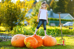 Cute little girl standing on huge pumpkins Royalty Free Stock Photo