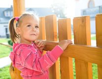 Cute little girl is standing near a fence Stock Photos
