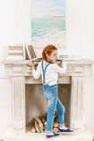 Cute little girl standing near fireplace with books and looking away Royalty Free Stock Image