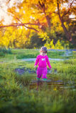 Cute little girl standing near a puddle. At summer evening Royalty Free Stock Image