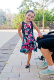 Cute little girl standing on one foot. Making faces for fun (sunset lighting Stock Photo