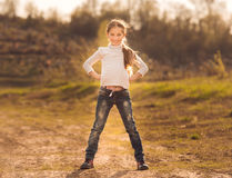 Cute little girl standing on a road. Cute little girl standing with hands to sides on a road in countryside Royalty Free Stock Photos