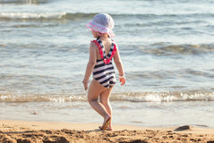 Cute little girl standing on summer beach Stock Images