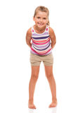 Cute little girl standing on white holding hands behind back Royalty Free Stock Image