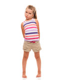 Cute little girl standing on white holding hands behind back Stock Photo