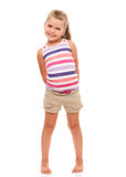 Cute little girl standing on white holding hands behind back Stock Image