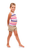 Cute little girl standing on white holding hands behind back Royalty Free Stock Photo