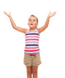 Cute little girl standing on white stretching her arms up. There is something big above me Stock Photo
