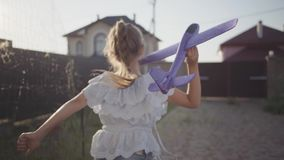 Cute little girl standing in the yard holding a toy plane in her hand. The child preparing to launch the toy airplane.  stock video footage