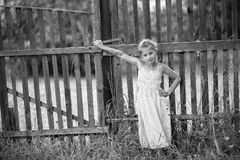 Cute little girl stands near a fence in the village. Stock Photos