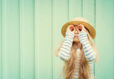 Cute little girl stands near a turquoise wall in boater hat and  looks invented binoculars. Space for text Royalty Free Stock Photo