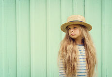 Cute little girl stands near a turquoise wall in boater hat and pensively looks aside. Space for text. Negative space Stock Photos