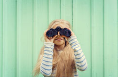 Cute little girl stands near a turquoise wall and looks binoculars. Space for text Stock Image