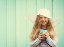 Cute little girl stands near a turquoise wall in white hat and holding cup. Space for text Stock Image