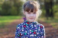 Cute little girl stands in sunny green park Stock Photography