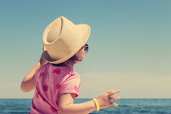 Cute little girl in a straw hat on the beach. Stock Photo