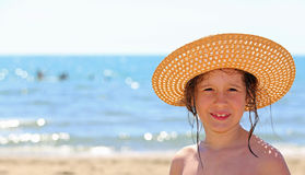 Cute little girl with straw hat by the sea Royalty Free Stock Photos