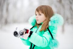 Cute little girl stretches her hand to catch falling snowflakes. First snow royalty free stock photo