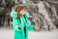 Cute little girl stretches her hand to catch falling snowflakes. First snow royalty free stock photos