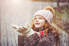 Cute little girl stretches her hand to catch falling snowflakes. Royalty Free Stock Images