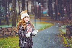 Cute little girl stretches her hand to catch falling snowflakes. Stock Photos
