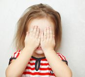 Cute little girl covers her face with palms stock images