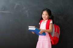 Cute little girl student holding heavy textbook stock photos