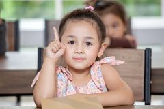 Cute little girl student pointing finger up in classroom school . Genius kid. Great idea . child clever sitting at desk preschool. Early education . Children stock images