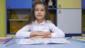 Cute little Girl Studying at the Library Doing Homework and Smiling. Elementary school. Child reading. Cute little girl studying at the library and smiling stock footage