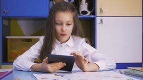 Cute little Girl Studying at the Library Doing Homework with tablet PC. Elementary school. Child reading. Cute little girl studying at the library and smiling stock video