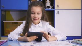 Cute little Girl Studying at the Library Doing Homework with tablet PC. Elementary school. Child reading. Cute little girl studying at the library and smiling stock footage