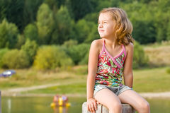 Cute little girl on stump Royalty Free Stock Images