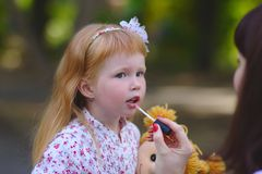 Cute Little girl in the summer park. Cute Little redhead girl in the summer park Royalty Free Stock Images