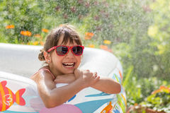 Cute little girl in sunglasses awash in an inflatable pool. In the garden Stock Photography