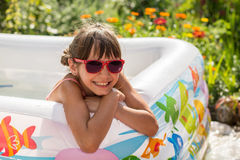 Cute little girl in sunglasses awash in an inflatable pool. In the garden Stock Images