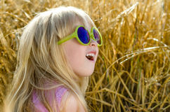 Cute little girl in sunglasses with a look of awe. Cute little girl sunglasses with look of awe and amazement on her face looking up into air her mouth open as Royalty Free Stock Photography