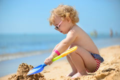 Cute little girl in sunglasses playing with sand. At ocean beach Royalty Free Stock Photos