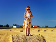 Cute little girl with sunglasses posing on the haystack Stock Images