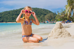Cute little girl in sunglasses and a swimsuit on the beach in paradise by the sea. Travel and Vacation. Freedom Concept royalty free stock image