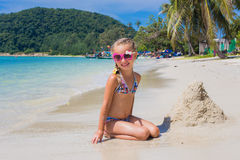 Cute little girl in sunglasses and a swimsuit on the beach in paradise by the sea. Travel and Vacation. Freedom Concept Stock Photos
