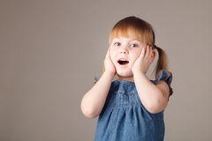 Cute little girl surprising on grey background Royalty Free Stock Photography