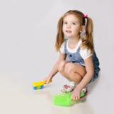 Cute little girl sweeps a floor Stock Photo